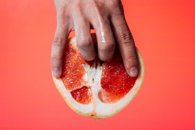 Person holding a red pomelo fruit. Two fingers are pushed inside suggestively.